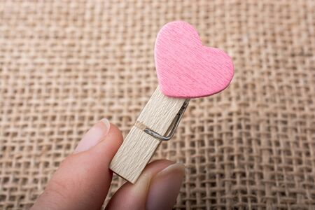 dearest: Colorful heart  attached to a clothespin in hand