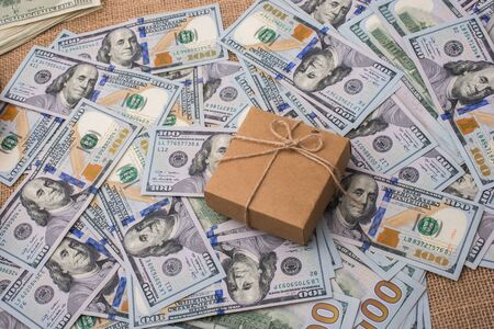 christmas debt: Gift box placed  is placed on spread US dollar banknotes