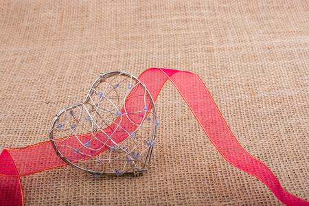 band and Heart shaped cage on linen canvas Stock Photo