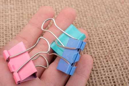 Colorful clips in hnad on a linen canvas
