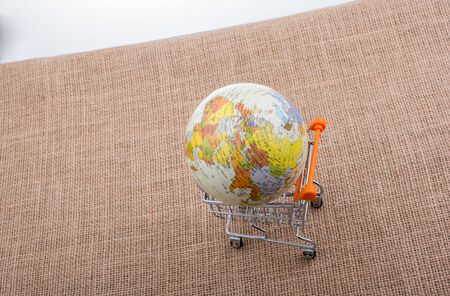 Globe in a shopping trolley on canvas Stock Photo