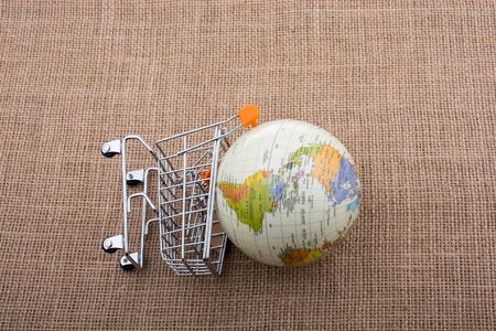 Globe with shopping trolley on thir sides on canvas Stock Photo