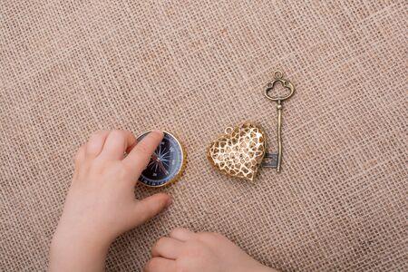 Compass, key and a heart shaped object  beside a hand