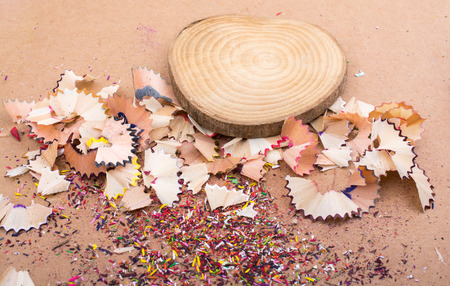 Colorful pencil shavings and a piece of wood