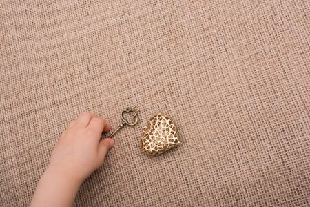 Heart shaped gold color metal object  beside a hand