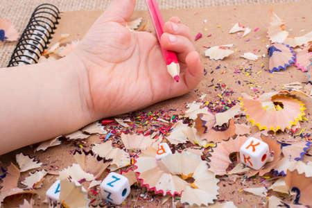 Red Color Pencil over  pencil shavings Stock Photo