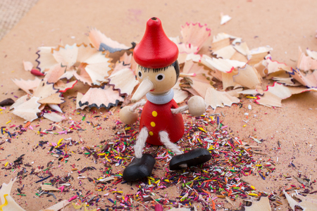 Pinocchio doll sitting amid pencil shavings