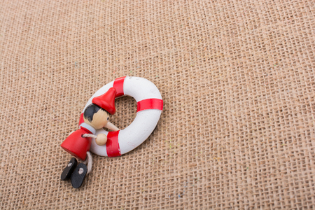 Pinocchio doll tied to a life preserver on canvas