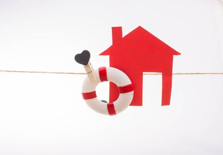 Model house and a life preserver with a heart on a string