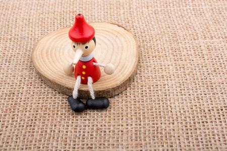 Pinocchio zittend op hout op doek achtergrond Stockfoto