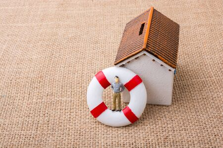 Model house and a life preserver with a man figure on it
