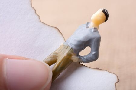 Man figurine held in hand on canvas Stock Photo