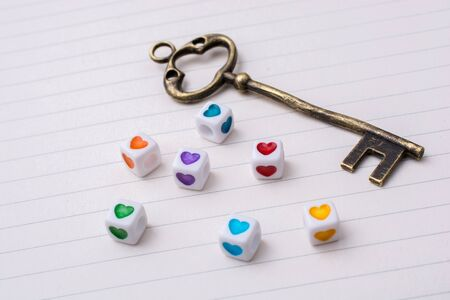 Key and colorful cubes with a heart placed on paper