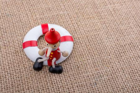 Pinocchio-Puppe an einen Rettungsring auf Leinwand gebunden Standard-Bild - 85554038