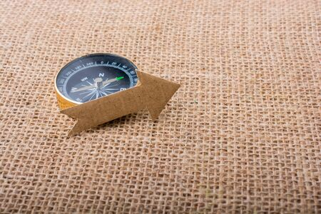 figurines: Compass and  paper arrow on a canvas background