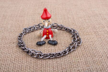 Chain around  wooden Pinocchio doll sitting on canvas background