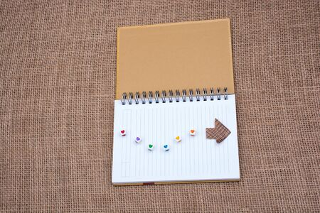 Love cubes and paper arrow on a notebook on canvas