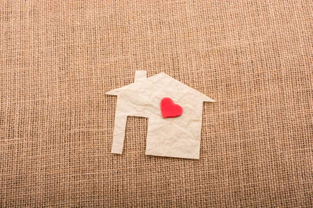 figurines: Heart shape on house shape cut out of paper with a canvas background