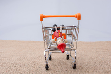 Pinocchio sitting on shopping trolley on a canvas background