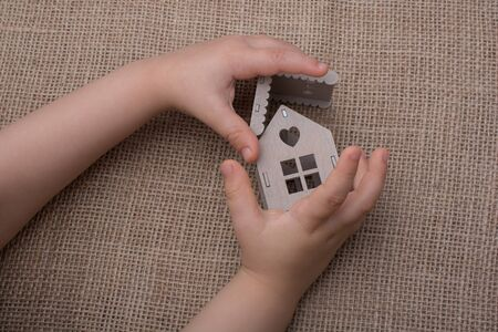 figurines: Child holding a model house on a linen canvas Stock Photo