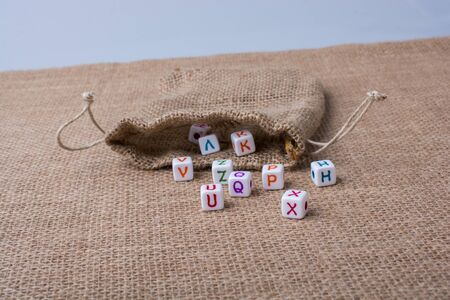 Colorful alphabet letter cubes out of sack on a canvas Stock Photo