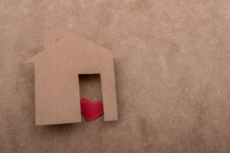 figurines: Little house shape cut out of paper and a heart on a canvas background