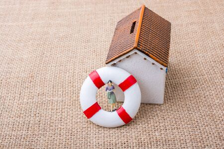 Model house and a life preserver with a woman figure on it