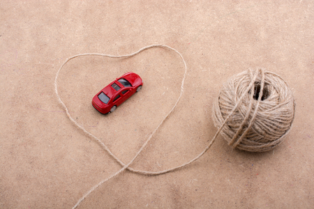 tred: TRed toy car and a spool of thread form a heart shape on background