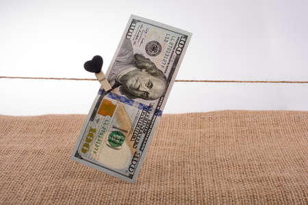American 100 dollar banknotes with a heart clip on a string