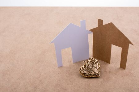 figurines: Heart shaped icon and paper houses on a brown background