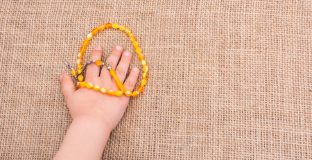 gods: Set of praying beads of various colors in hand on canvas