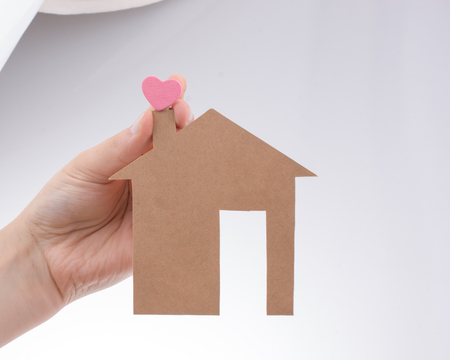 figurines: Hand holding a aper house on a canvas background Stock Photo