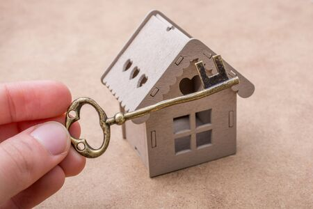 figurines: Retro key and a Model house on a canvas background Stock Photo