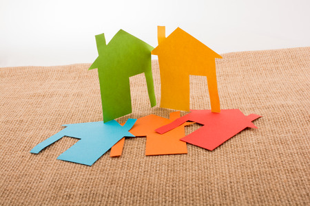 figurines: Little house shape cut out of colorful paper on a canvas background