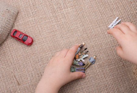 Key, toy cars, human figures and a sack on a canvas Stock Photo