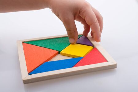 jigsaw tangram: hand holding a missing piece in a tangram puzzle Stock Photo