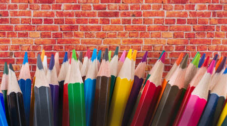 Color Pencils  of various colors  and brick wall on a  white background Stock Photo
