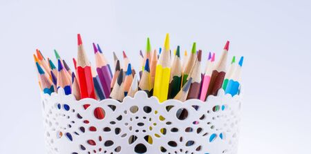 Colorful pencils in a vase on a white background