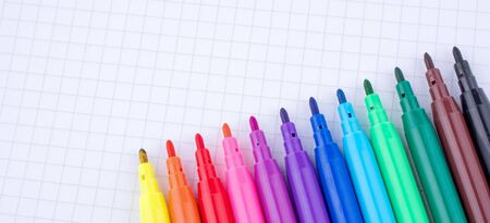 white sheet: Colorful felt-tip pens on a notebook Stock Photo