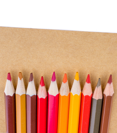 Color pencils  placed on  brown sheet of paper Stock Photo
