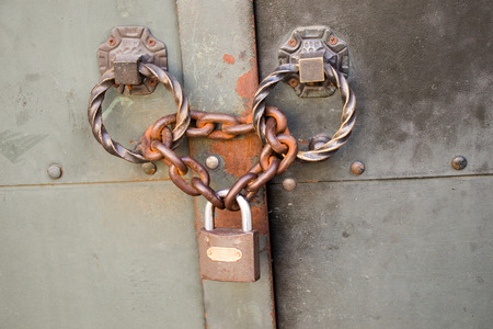 The Old rusted metal lock  in metal chains Stock Photo
