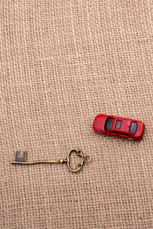 Key and a red toy car on a linen canvas Standard-Bild