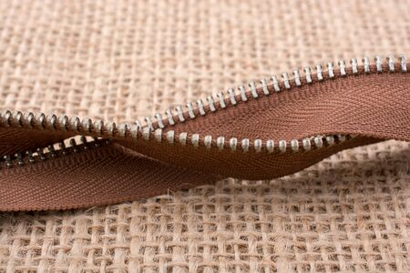 Parts of the brown color zipper on linen canvas background Stock Photo