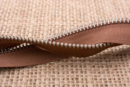 Parts of the brown color zipper on linen canvas background Standard-Bild
