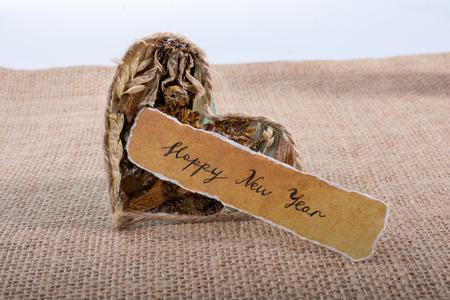 Happy new year written paper beside a heart shape