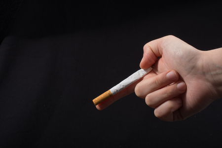 Hand  holding a cigarette like gun on black background Stock Photo