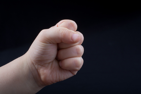 Hand closed for a fist gesture in black background