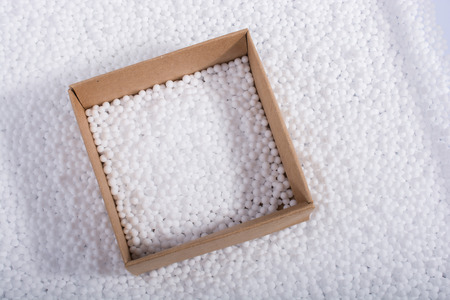 Box on little  white polystyrene foam balls Stock Photo