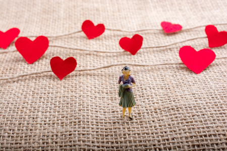 Woman figurine and Love concept with paper heart on  threads