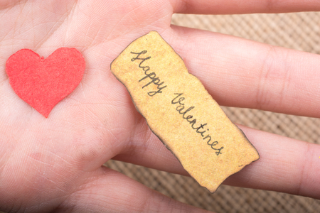 Love icon and Valentine's day wording on torn paper Standard-Bild